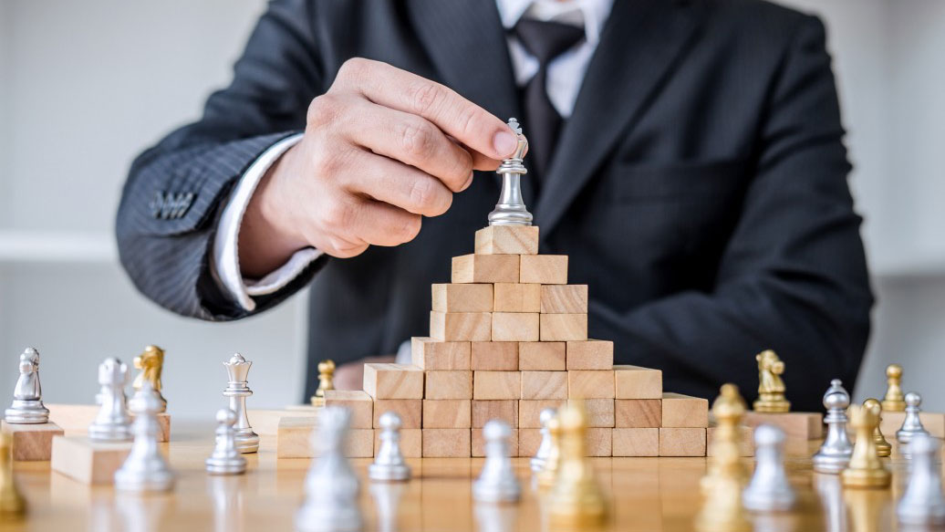 wooden-game-of-strategy-hands-of-confident-businessman-playing-chess-game-to-development-analysis-new_t20_E4RYXQ